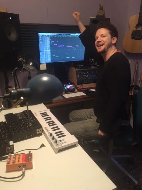 man celebrating surrounded by computer and keyboards