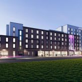 Moxy Bristol Hotel shown at night, a seven story building with a mix of red brick and pale render, white and pink lighting show up the exterior