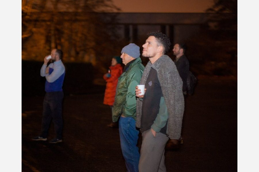 Community members outside in the night time looking at something out of shot