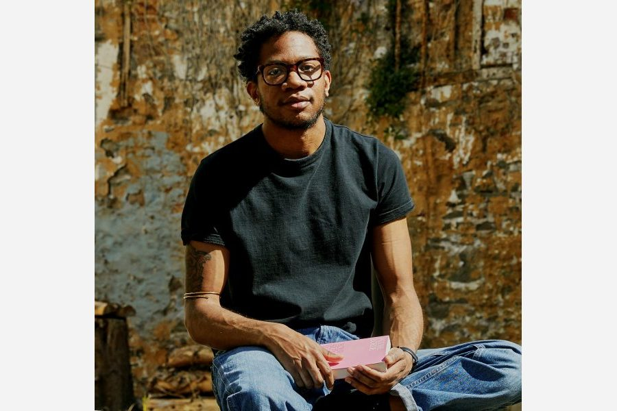 Photograph of Myles-Jay Linton, black person with black hair, glasses, black t-shirt and blue jeans sat in front of a rust coloured wall, holding a pink book