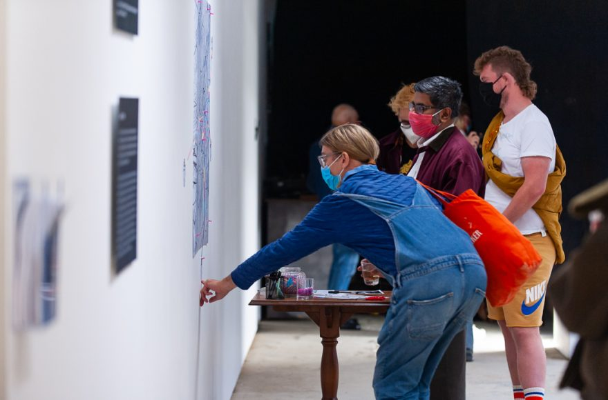 People looking at images on a wall.