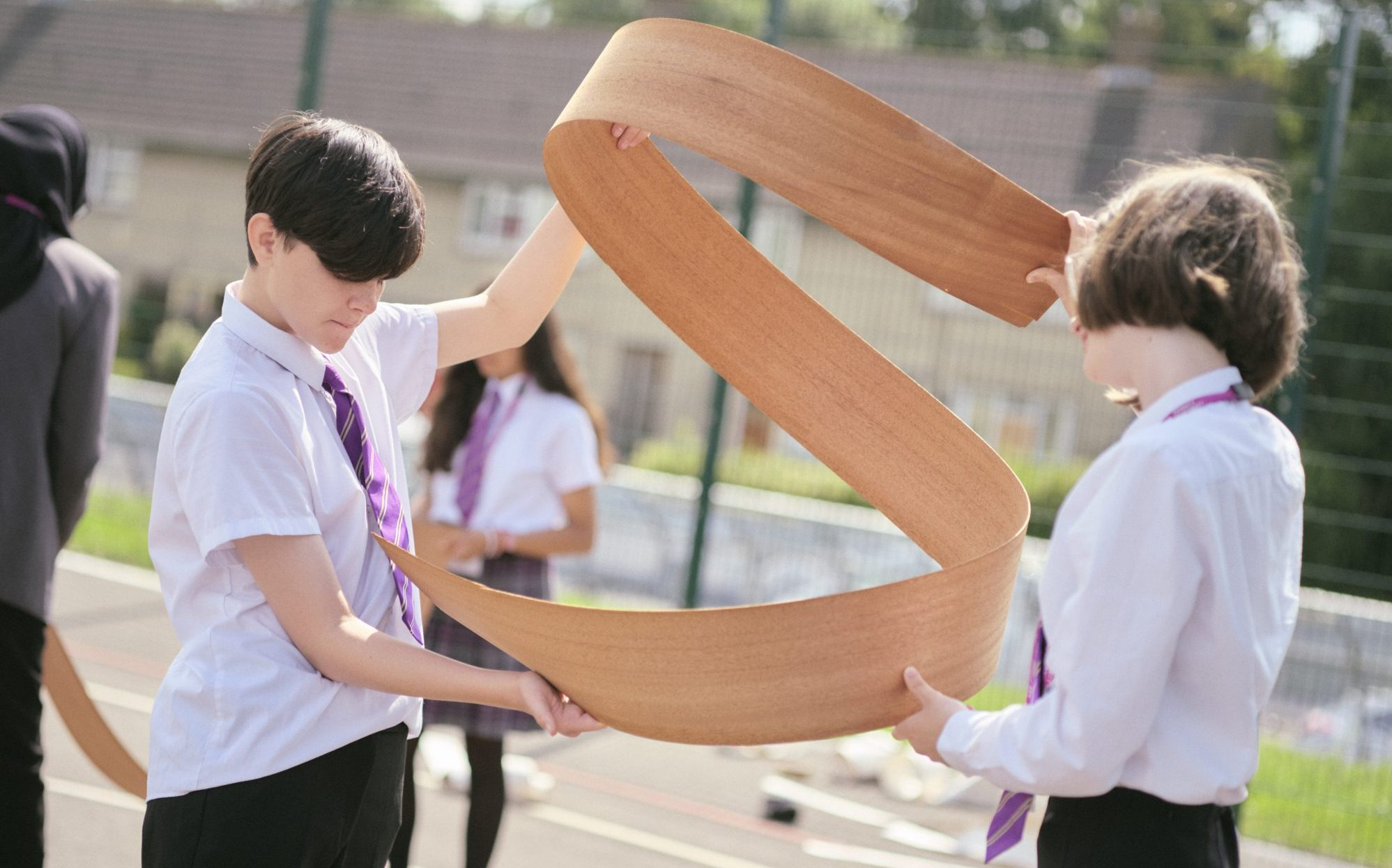 Two school pupils working with thin strip of wood to create helix shape
