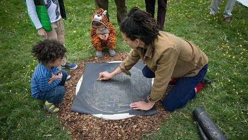 Kayle Brandon, woman making a brass rubbing with two children watching